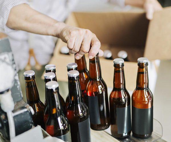 brewery-worker-preparing-beer-bottles-U498MD9